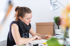 Young female artist drawing sketch using sketchbook with pencil at her workplace in studio. Side view portrait of stock images