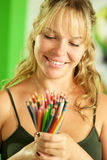 Young female artist looking at colored pencils and smiling Stock Images