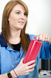 Young female artist opening red paint bottle Stock Image