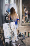 Young female artist painting abstract picture in studio, beautiful woman portrait Stock Images