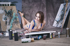 Young female artist painting abstract picture in studio, beautiful sexy woman portrait. Toned image Royalty Free Stock Image