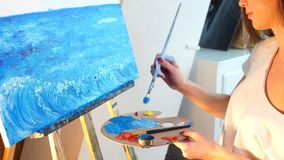A young female artist painting picture on canvas with blue oil paints in her workshop. stock footage