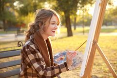 Young female artist painting picture. In autumn park Royalty Free Stock Image