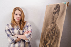 Young female artist posing beside her artwork Royalty Free Stock Photos