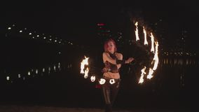 Young female artist spinning fire fans near river stock video