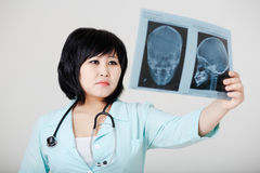 Young female Asian doctor with stethoscope looking Royalty Free Stock Photos