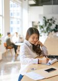 Young female Asian entrepreneur working in an open office.  royalty free stock photos