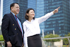 Young female Asian executive and senior Asian businessman looking at one direction Royalty Free Stock Image
