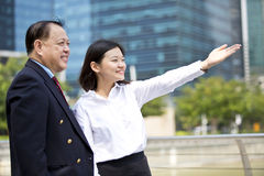 Young female Asian executive and senior Asian businessman looking at one direction. Outdoor Royalty Free Stock Photo