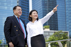 Young female Asian executive and senior Asian businessman looking at one direction. Outdoor Royalty Free Stock Image