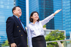 Young female Asian executive and senior Asian businessman looking at one direction. Outdoor Royalty Free Stock Photos