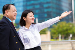 Young female Asian executive and senior Asian businessman looking at one direction Stock Photos
