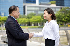 Young female Asian executive and senior Asian businessman shaking hands. Outdoor Royalty Free Stock Photos