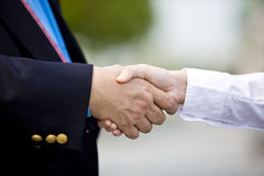 Young female Asian executive and senior Asian businessman shaking hands Stock Image