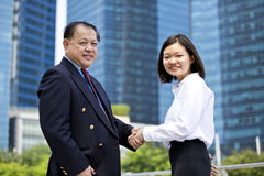 Young female Asian executive and senior Asian businessman shaking hands. Outdoor Royalty Free Stock Image