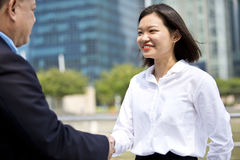 Young female Asian executive and senior Asian businessman shaking hands. Outdoor Stock Photos