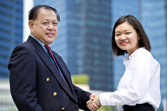 Young female Asian executive and senior Asian businessman shaking hands. Outdoor Stock Images