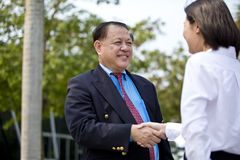 Young female Asian executive and senior Asian businessman shaking hands. Outdoor Stock Image