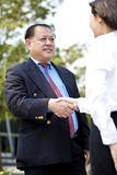 Young female Asian executive and senior Asian businessman shaking hands. Outdoor Royalty Free Stock Photo