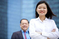 Young female Asian executive and senior Asian businessman smiling portrait. Outdoor Royalty Free Stock Photography