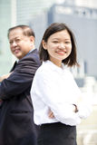 Young female Asian executive and senior Asian businessman smiling portrait. Outdoor Stock Photos
