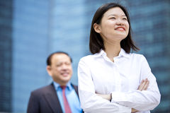 Young female Asian executive and senior Asian businessman smiling portrait royalty free stock image
