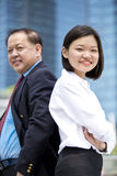 Young female Asian executive and senior Asian businessman smiling portrait. Outdoor Stock Images