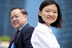 Young female Asian executive and senior Asian businessman smiling portrait Stock Photography