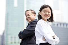 Young female Asian executive and senior Asian businessman smiling portrait. Outdoor Royalty Free Stock Photo