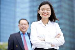 Young female Asian executive and senior Asian businessman smiling portrait. Outdoor Royalty Free Stock Image