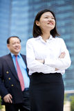Young female Asian executive and senior Asian businessman smiling portrait. Outdoor Stock Photo