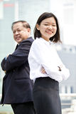 Young female Asian executive and senior Asian businessman smiling portrait. Outdoor Stock Photography