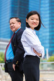 Young female Asian executive and senior Asian businessman smiling portrait Stock Photo