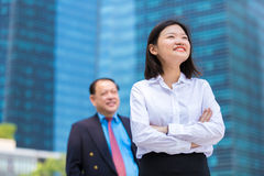 Young female Asian executive and senior Asian businessman smiling portrait. Outdoor Royalty Free Stock Photos