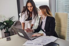 Young female assistant consulting with a top manager showing data on laptop screen and asking for advice sitting at royalty free stock image