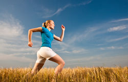 Young female athelte running across the field Stock Photo