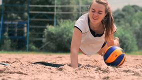 Young female athlete dives into the sand and saves a point during beach volleyball match. Cheerful Caucasian girl jumps. And crashes into the white sand during stock footage