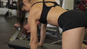 Young female athlete doing dumbbell row exercise in gym indoors. Fitness woman perfect physical shape, trains in sports club with iron equipment. Classical stock video footage