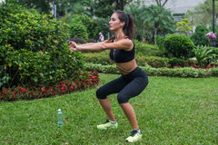 Young female athlete doing squat exercises outdoors in park. Fit girl working out her core and glutes with bodyweight. Stock Image