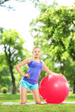 Young female athlete exercising with a ball in park Stock Photo