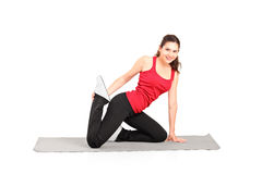 A young female athlete exercising on a mat Royalty Free Stock Images