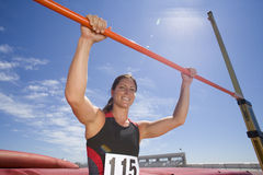 Young female athlete with hands on bar, low angle view (lens flare) Stock Images