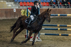 Young female athlete horse galloping across field  sports complex Royalty Free Stock Photography