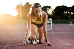 Young female athlete launching off the start line in a race. Royalty Free Stock Image