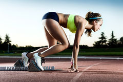 Young female athlete launching off the start line in a race. royalty free stock photography