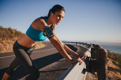 Young female athlete leaning on guardrail. Young female athlete leaning on highway guardrail looking away. Woman runner outdoors on country road taking a break Stock Photo