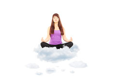 Young female athlete in outfit sitting on clouds and meditating. Isolated on white background Royalty Free Stock Photo
