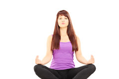 Young female athlete in outfit sitting on a floor and meditating. Isolated on white background Stock Image