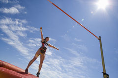 Young female athlete preparing to jump over bar, low angle view (lens flare) Royalty Free Stock Photo