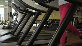 Young female athlete quickly runs along treadmill in the gym. Beautiful slender lady performs cardio training on sports equipment in fitness club stock video footage